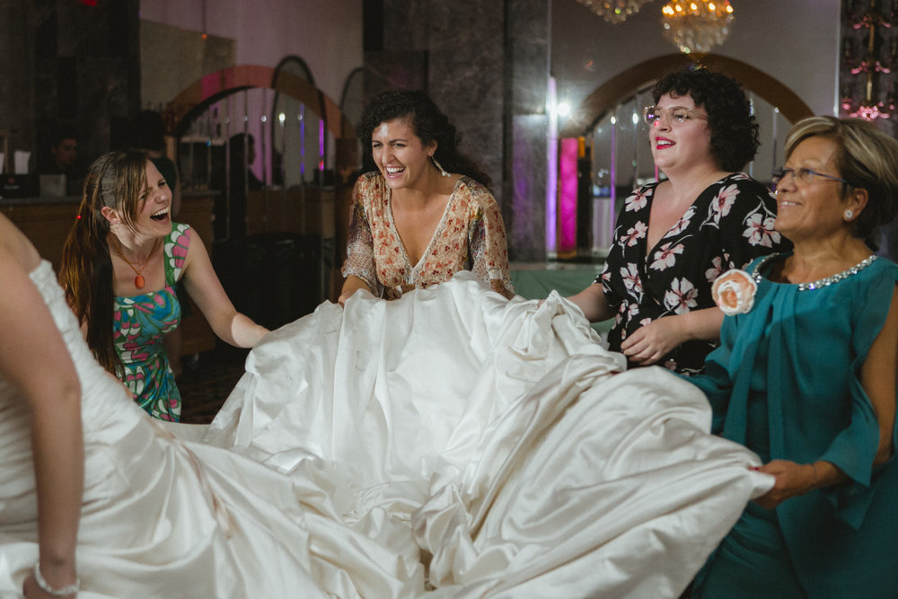 Guests laugh while holding bride's train while she dances | Scavello's on the Island | Manhattan wedding | Bronx Wedding | Cathy & Antonello's wedding | Amy Sims Photography