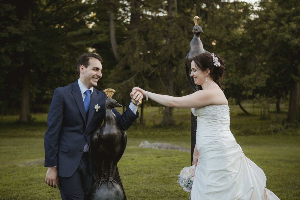 Couple smile at each other holding hands, posing with peacock statue | Bartow-Pell Mansion wedding | Manhattan wedding | Bronx Wedding | Cathy & Antonello's wedding | Amy Sims Photography