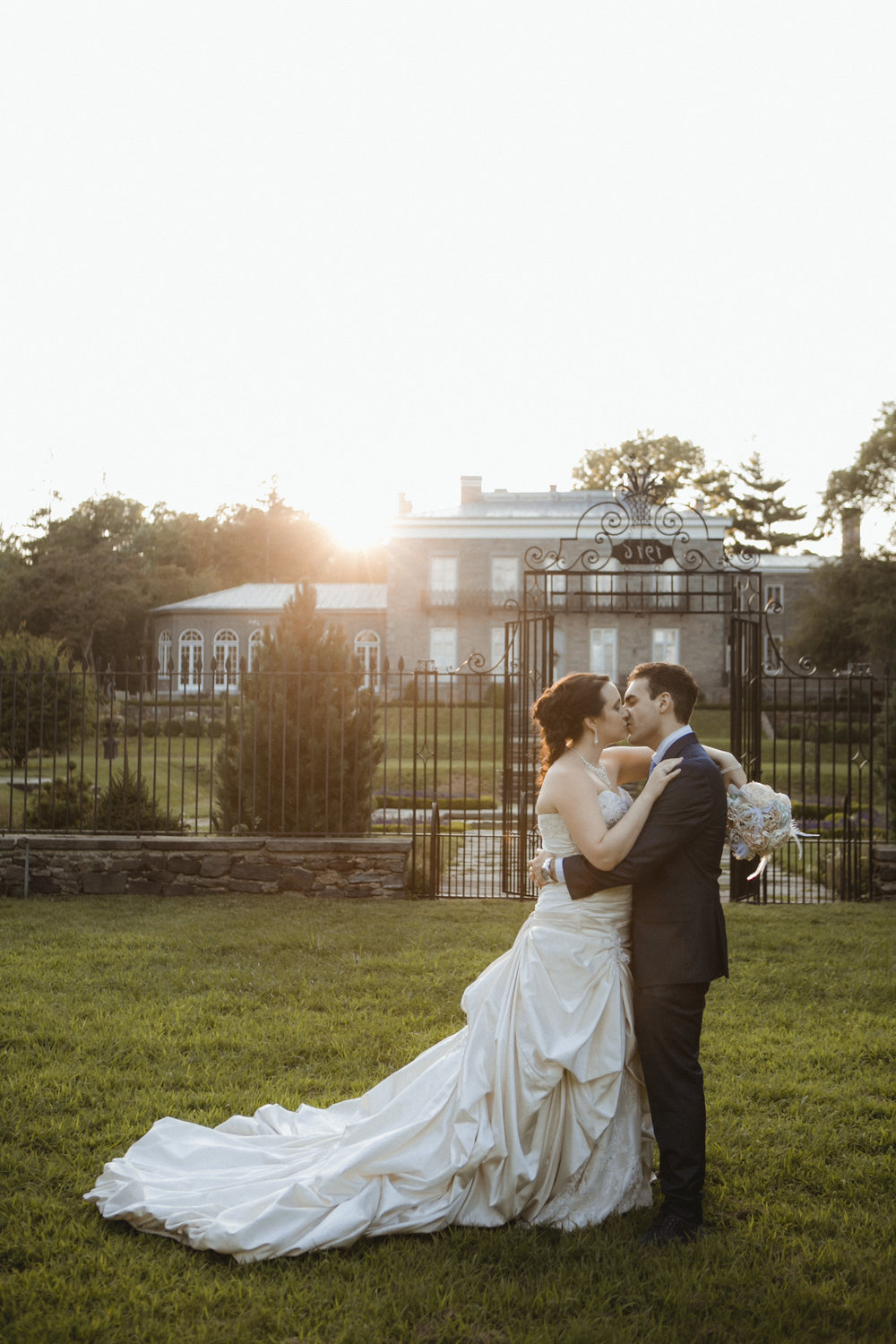 Couple share a kiss at sunset | Maggie Sottero gown | Sean John suit | Bartow-Pell Mansion wedding | Manhattan wedding | Bronx Wedding | Cathy & Antonello's wedding | Amy Sims Photography