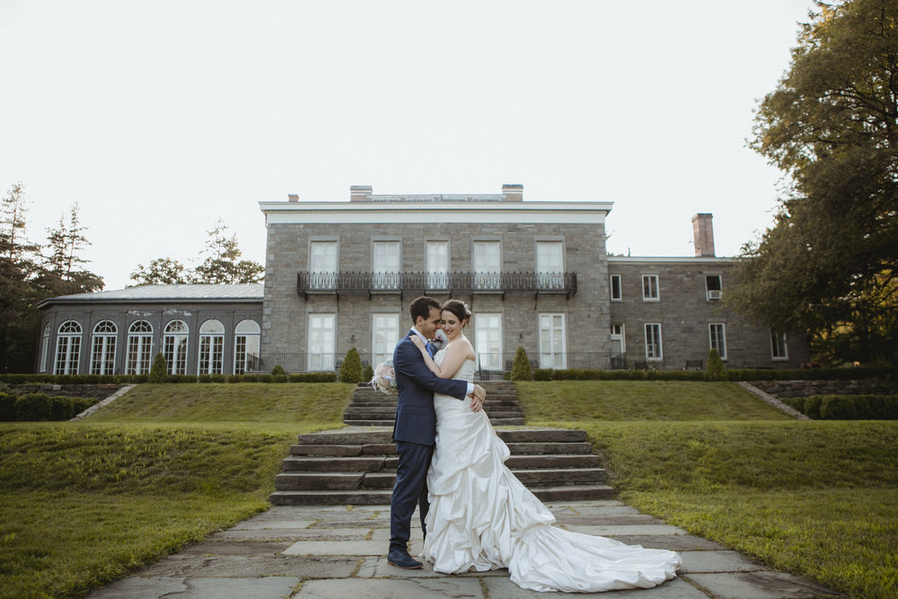 Couple embraces in front of Bartow-Pell Mansion | Maggie Sottero gown | Sean John suit | Manhattan wedding | Bronx Wedding | Cathy & Antonello's wedding | Amy Sims Photography