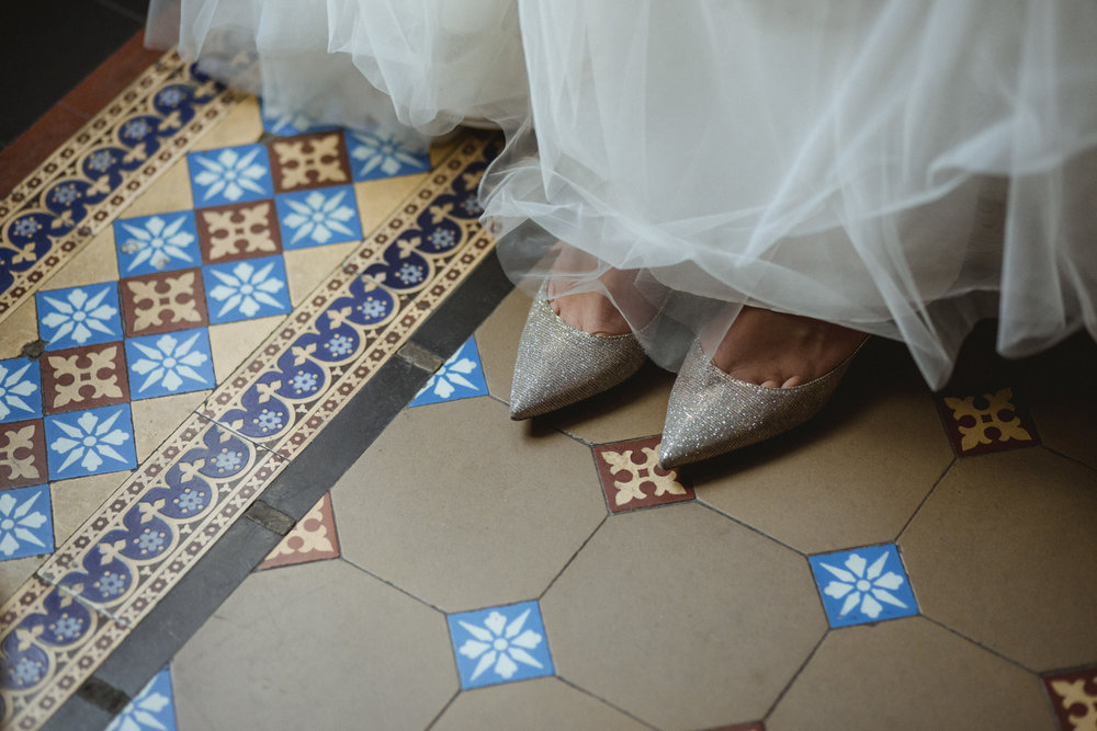 Amy Sims Photography | Bride's pointed shoes peak out from tulle from her dress, standing on ornate tile | Brooklyn Wedding Photographer | Weylin Wedding