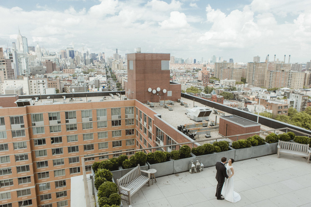 Amy Sims Photography | Bride and Groom stand together on rooftop with the Manhattan skyline around them | Public Hotel Wedding | Manhattan Wedding Photographer | New York Wedding Photographer