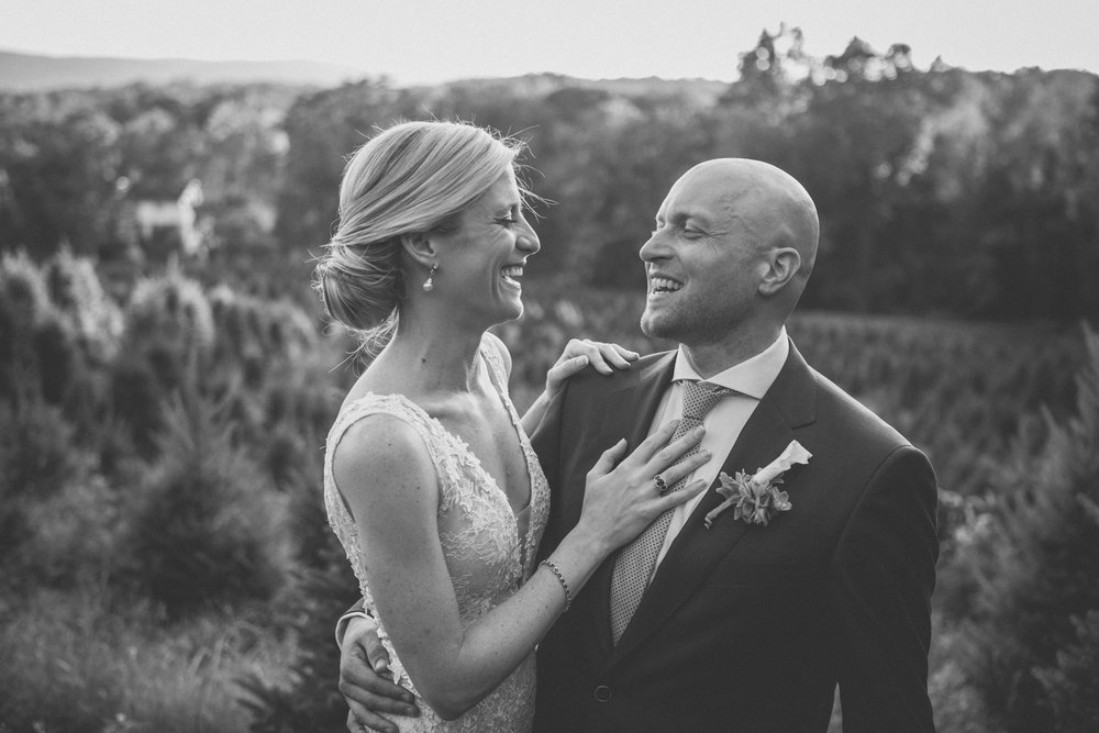 Amy Sims Photography | Bride and Groom hold each other while laughing in a field Christmas trees | Emmerich Tree Farm Wedding | black and white photography | Hudson Valley Wedding photographer |