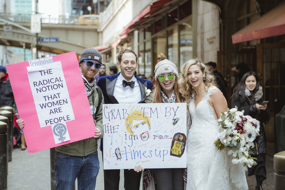 Amy Sims Photography | Bride and groom pose with couple holding signs for the women's march | New York Wedding Photographer | Manhattan Wedding Photographer | Grand Central Station portraits