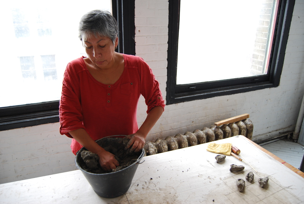 Rebecca Belmore in her studio with clay gumbo from the Red River Valley.