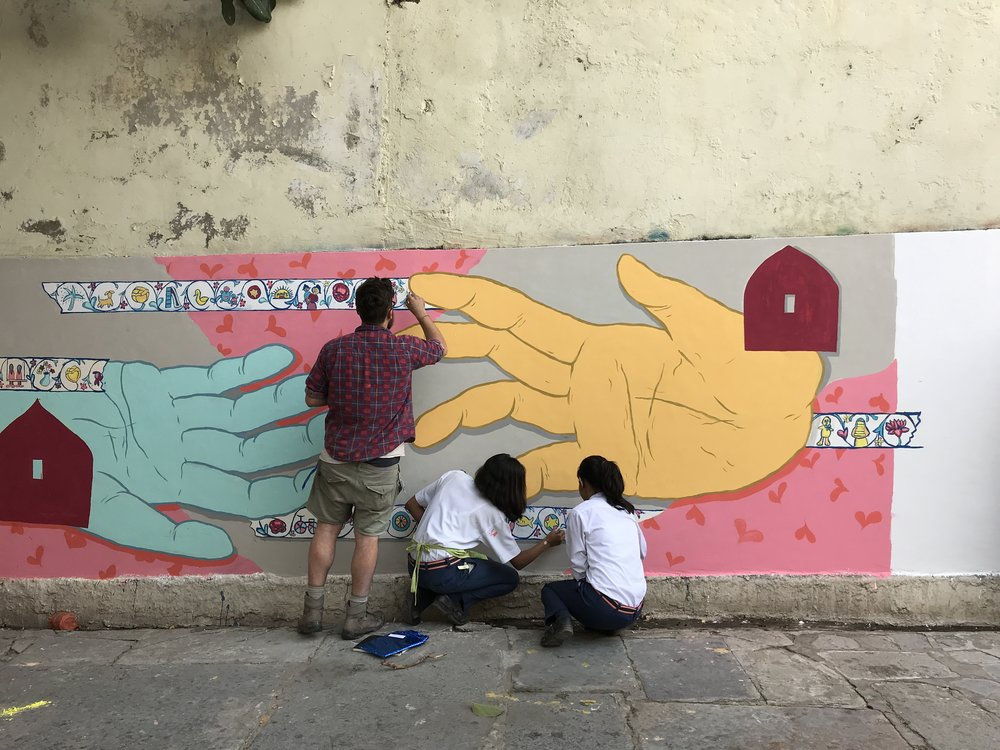 Jake Holmes working on a mural with students at Maharana Mewar Public School in Udaipur. Photo by Zoe Freney.
