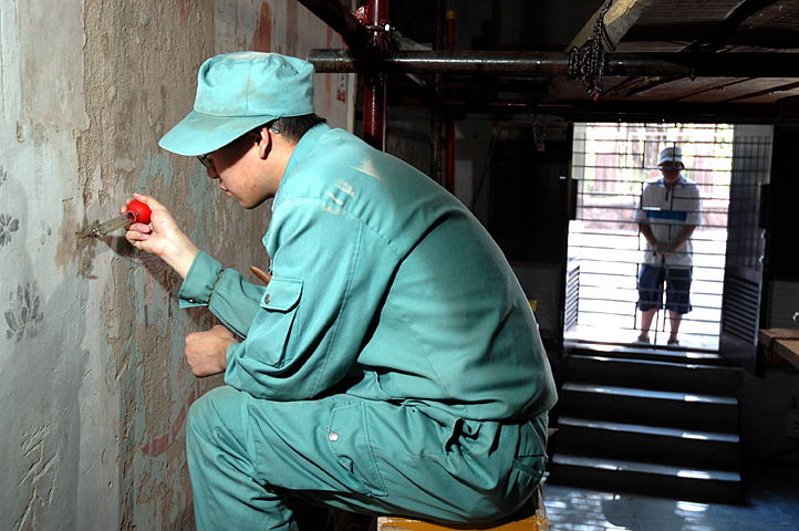 A conservator works on a mural as a tourist looks on.