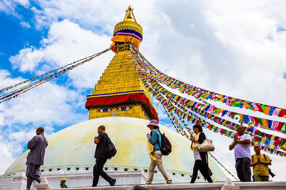 Pilgrims circumambulating the Boudhanath stupa. 14th century. Kathmandu, Nepal. Image by Alina Chan from  Wiki Commons .