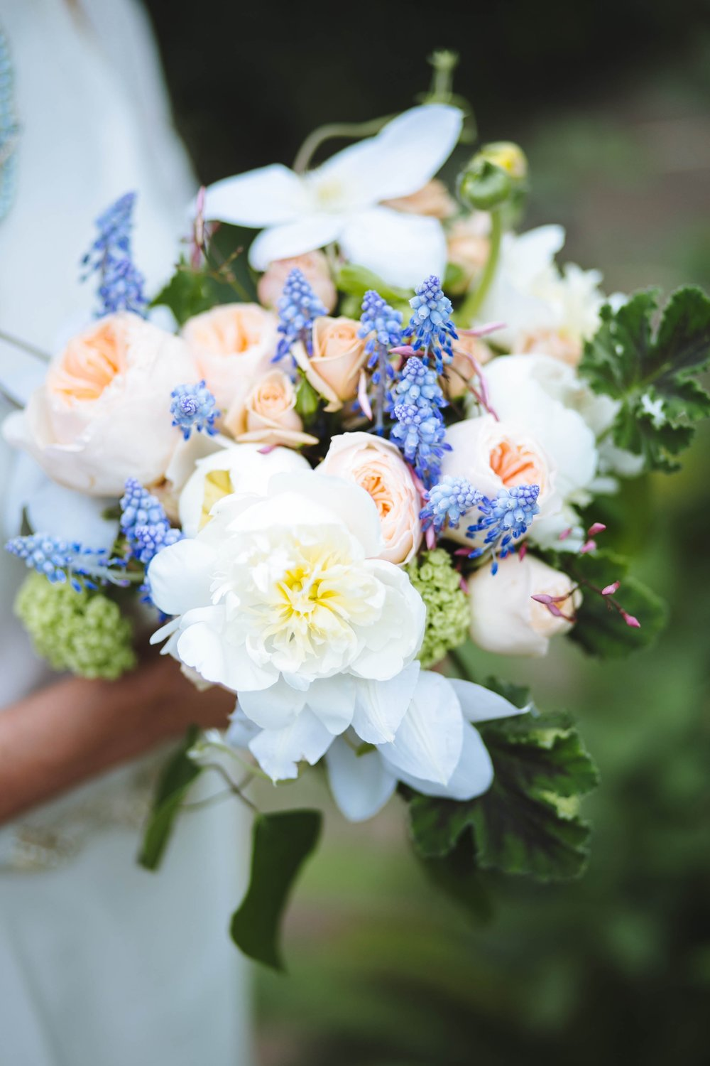 Wedding bouquet designed by Fleur Inc with muscari, clematis & peonies.  Photographed by Jaclyn Simpson Photography.