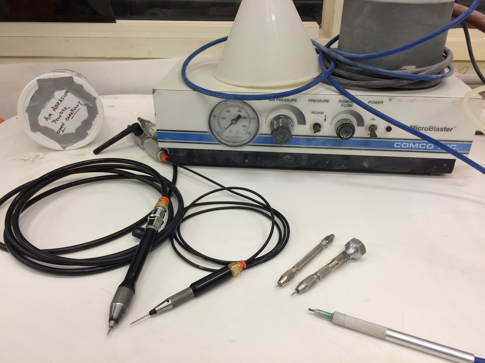 The tools on the left connected to air hoses are micro-jacks. The two silver tools to their right are pin vises. The tool on the far right is for air abrasion.