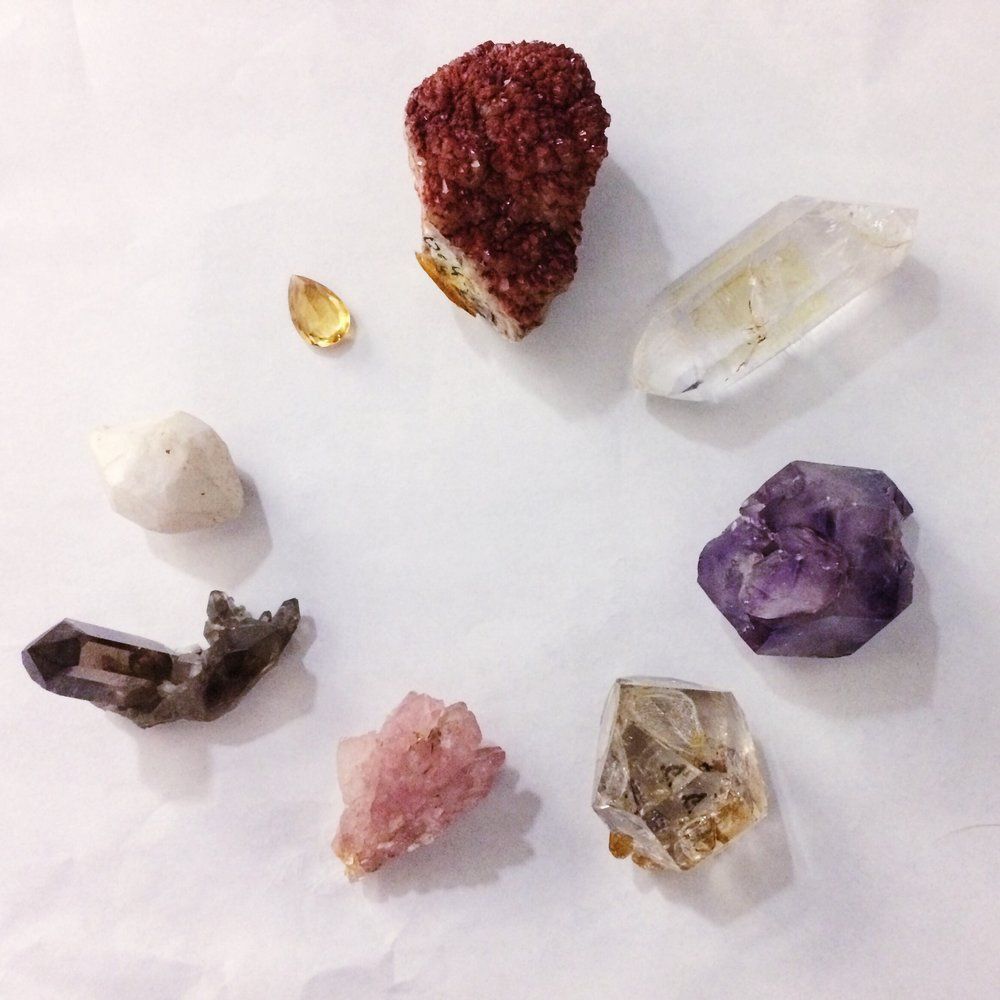 Quartz varieties from the Bruce Museum's mineral collection. Starting at the top, moving counterclockwise: Harlequin quartz, quartz, amethyst, herkimer diamond (quartz), rose quartz, smoky quartz, milky quartz, and citrine. Photo by Haley Royer.