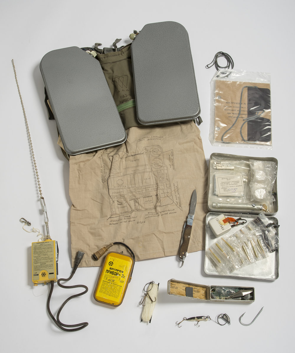 This is our NAZ-7 pilot survival kit on display. It contains: A kulikov antenna, a handheld radio beacon, a priboy battery, water flasks, a NAZ-7 bag, a folding knife, a box of signal flares, sunglasses, a can opener, dry fuel, an alarm mirror, a flashlight with a spare bulb, a box of gun cartridges, matches, fishing tackle. Photo by Paul Mutino