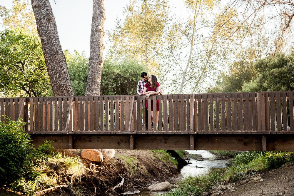 old-wooden-bridge-couple-embrace-engagement-session-burgandy-plaid-san-diego-photographer-sophia-elizabeth-wedding-photography-old-poway-park-california