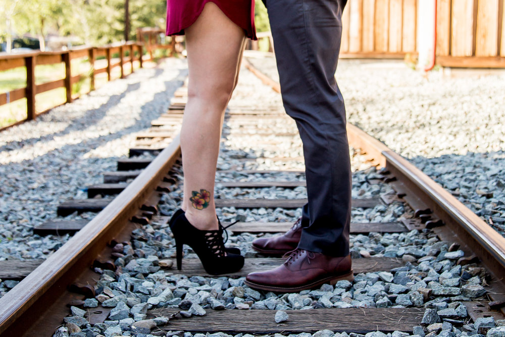 feet-on-train-tracks-at-old-poway-park-san-diego-calitfornia-vintage-engagement-session-tattoo-ankle-dress-shoes-slacks