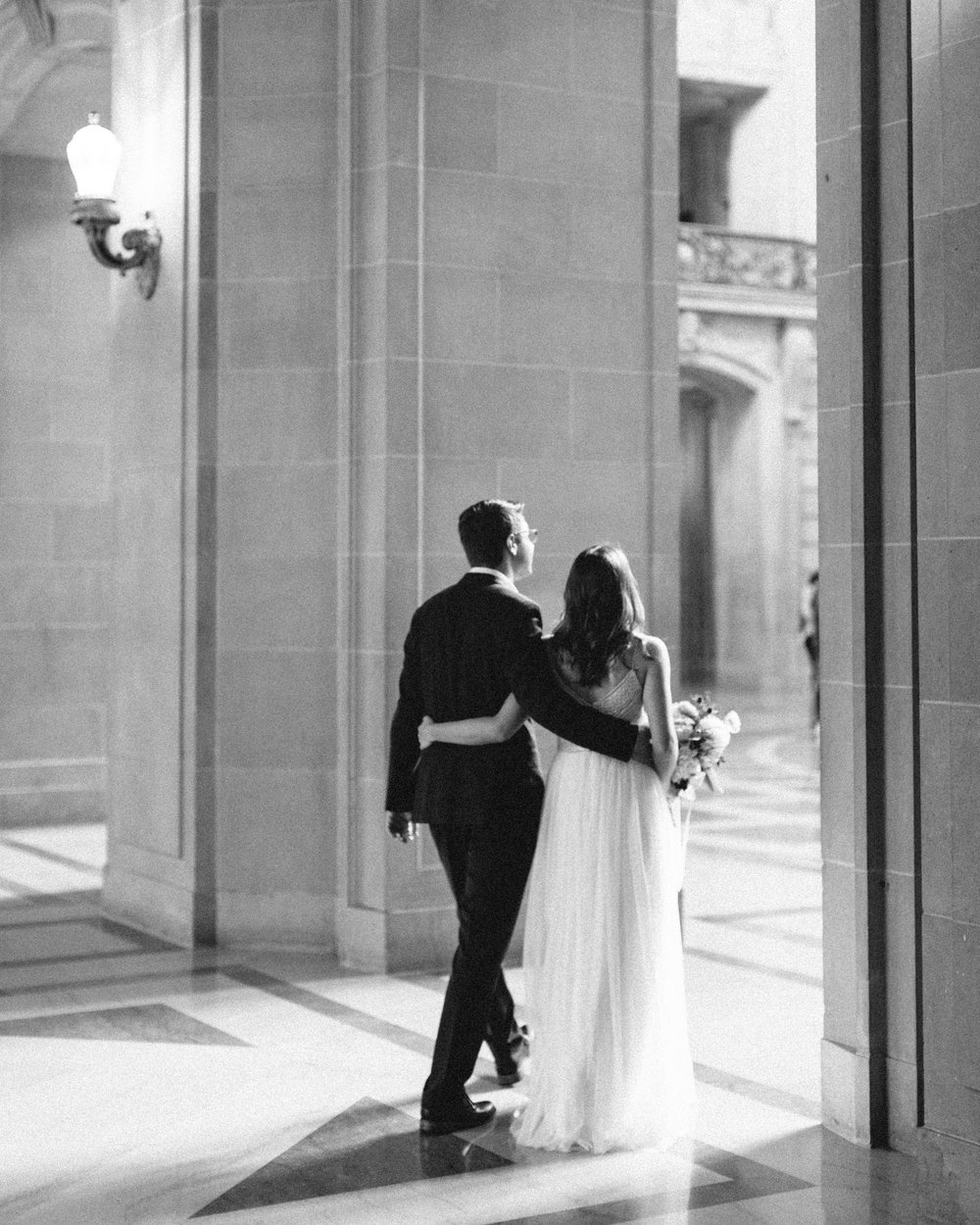 Brandon Sampson Photography. Bride and Groom walking in San Francisco City Hall. Film Photography.
