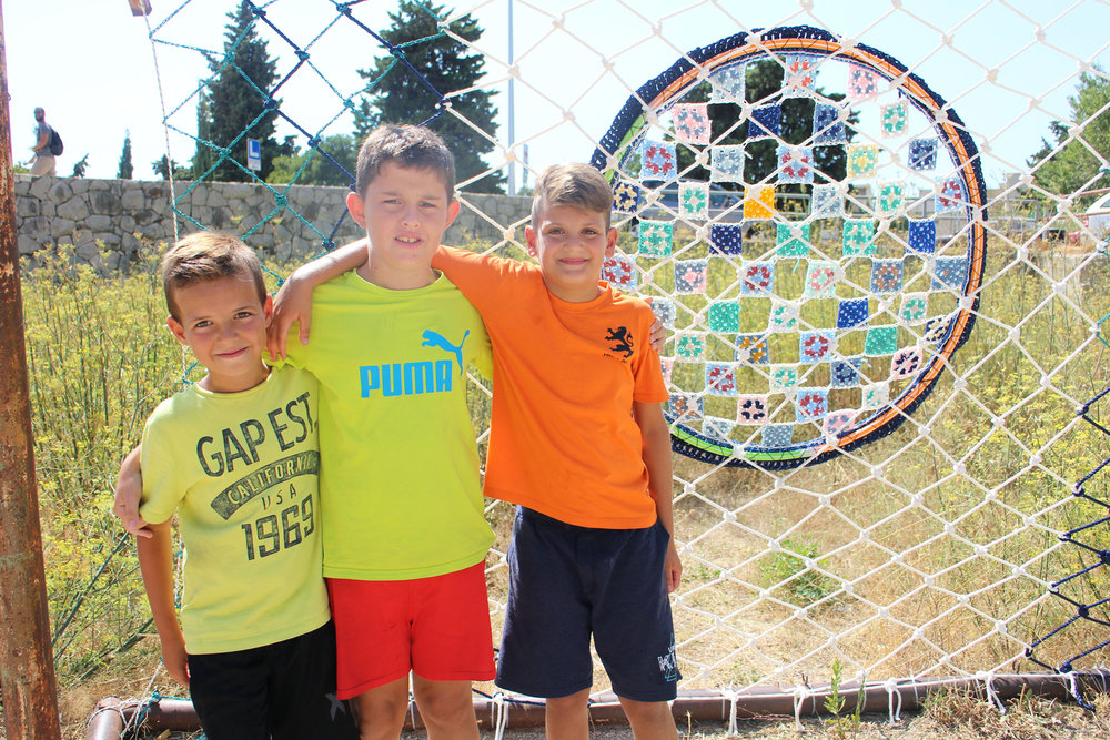 Neighborhood kids enjoy a macramé soccer net adorned with the emblem of local soccer club Hadjuk.