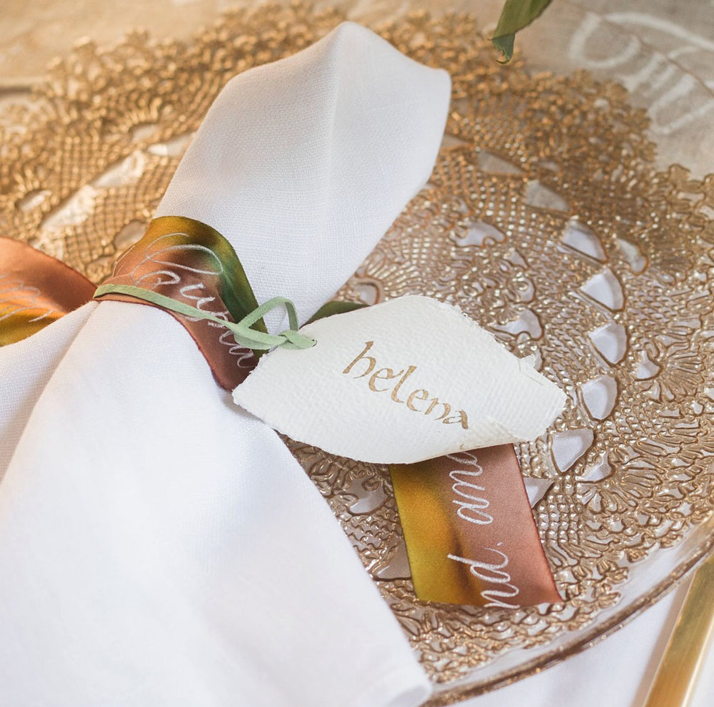 Calligraphy place setting: historic Carolingian script on a scroll place card, with brush script on a silk ombre ribbon around the napkin // designed and calligraphed by Chavelli www.chavelli.com // photo by Rebecca Jeanson www.rjimagery.com