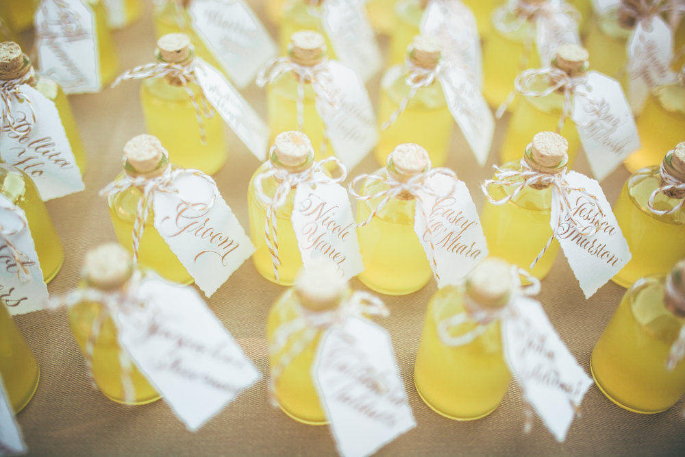 Gold calligraphy on deckled edged tags on mini limoncello bottles for a gorgeous Lake Como wedding // calligraphy by www.chavelli.com