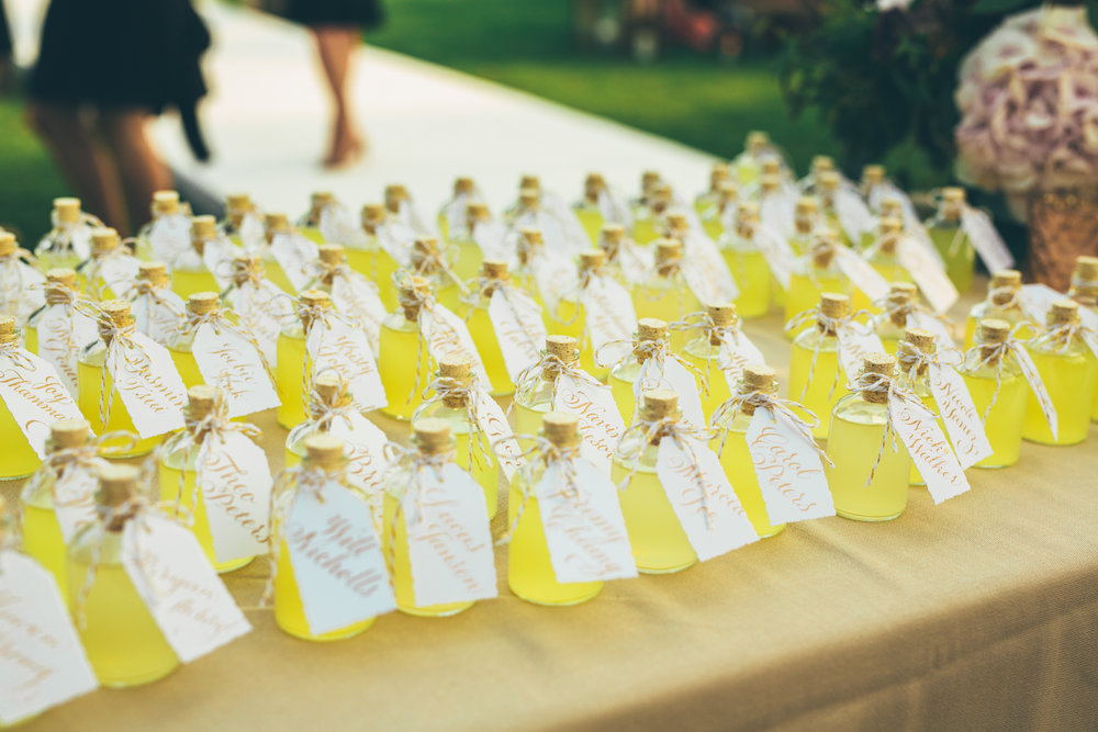 Hand-calligraphy escort tags on limoncello bottles at an elegant Lake Como wedding in Italy // by Studio Chavelli www.chavelli.com