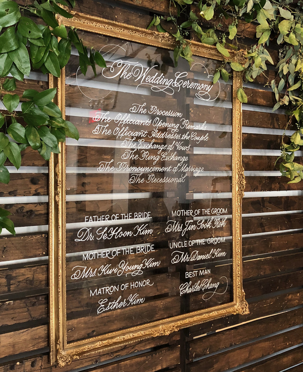 Wedding ceremony program calligraphy on acrylic with an ornate gold frame | by www.chavelli.com
