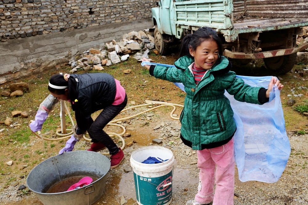 Young girls wash laundry in their front yard in a Tibetan region of China.