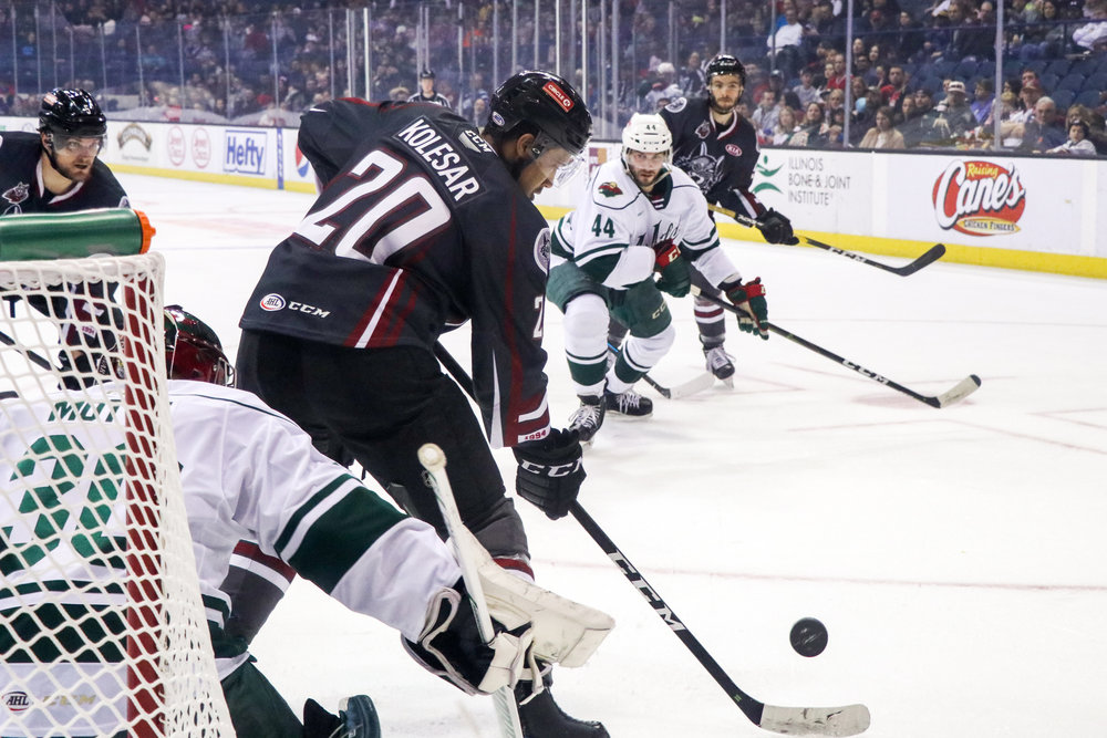 Chicago Wolves player Keegan Kolesar (20) keeps the puck away from Iowa Wild player Matt Bartkowski (44). The Chicago Wolves won 2:1 in overtime.