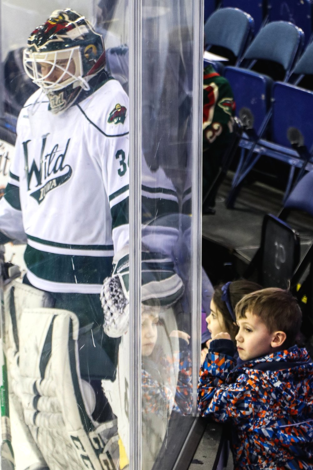 Iowa Wild goalie C.J. Motte and two young fans watch the rink during warmups.