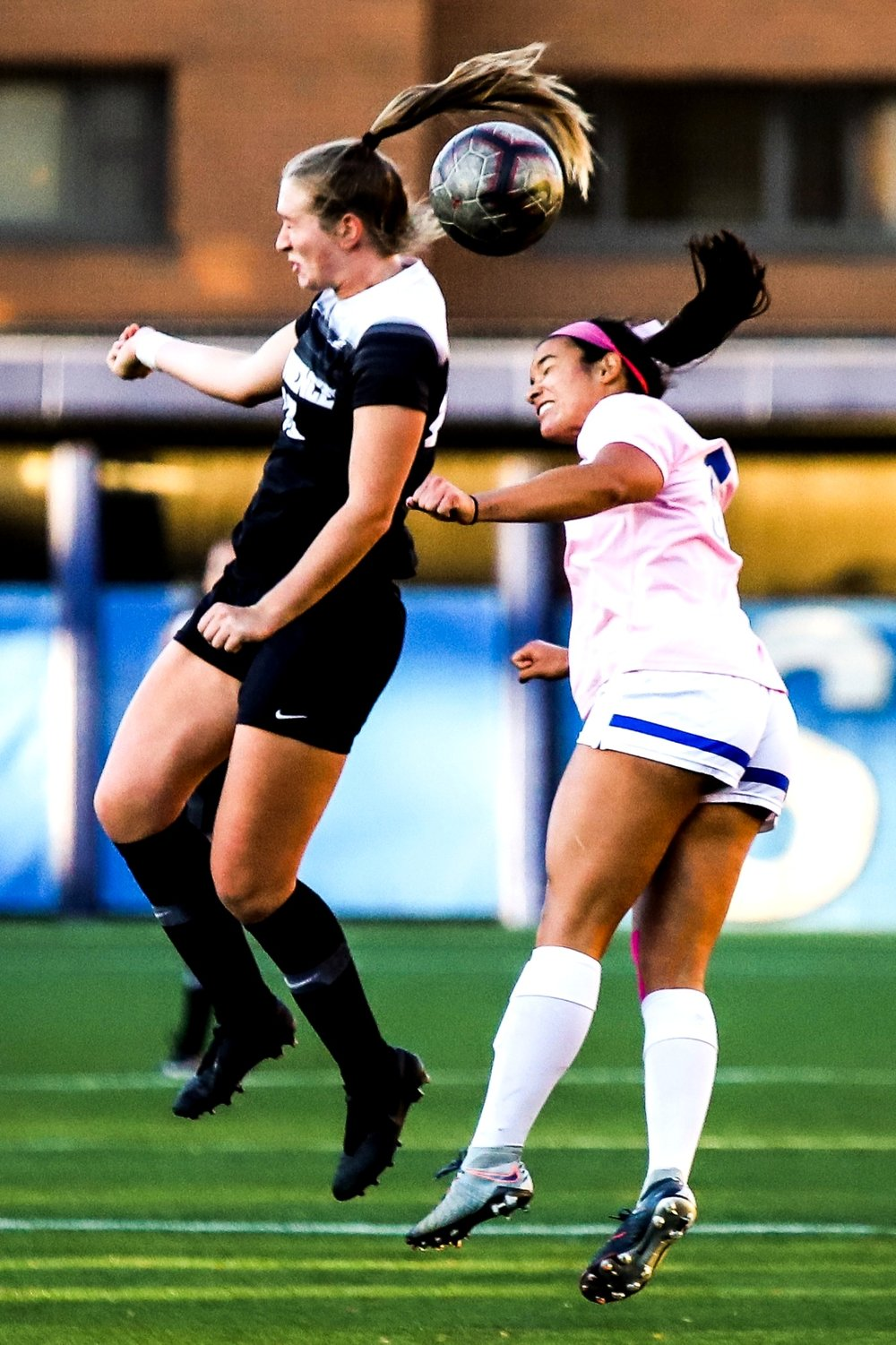 A Providence player and a DePaul player both jump to headbutt the ball.