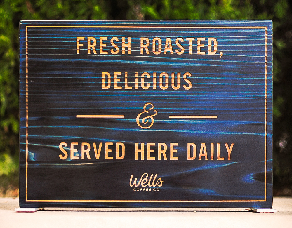 Custom laser engraving and etching on shou sugi ban cypress wood sign for Florida-based Wells Coffee Company. Aluminum stands.