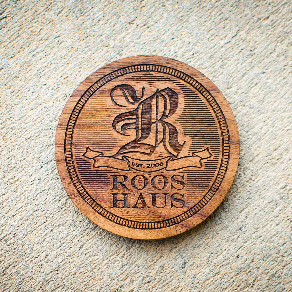 Custom laser engraved and cut wood coasters. Made of walnut with custom logo.