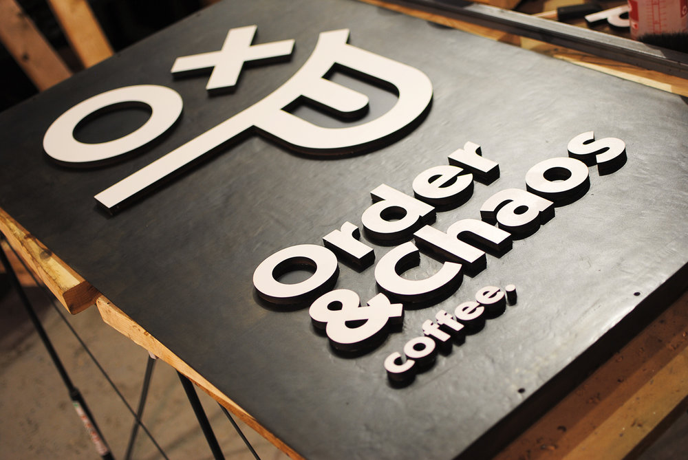 Order & Chaos coffee shop sign made out of laser cut steel and wood.