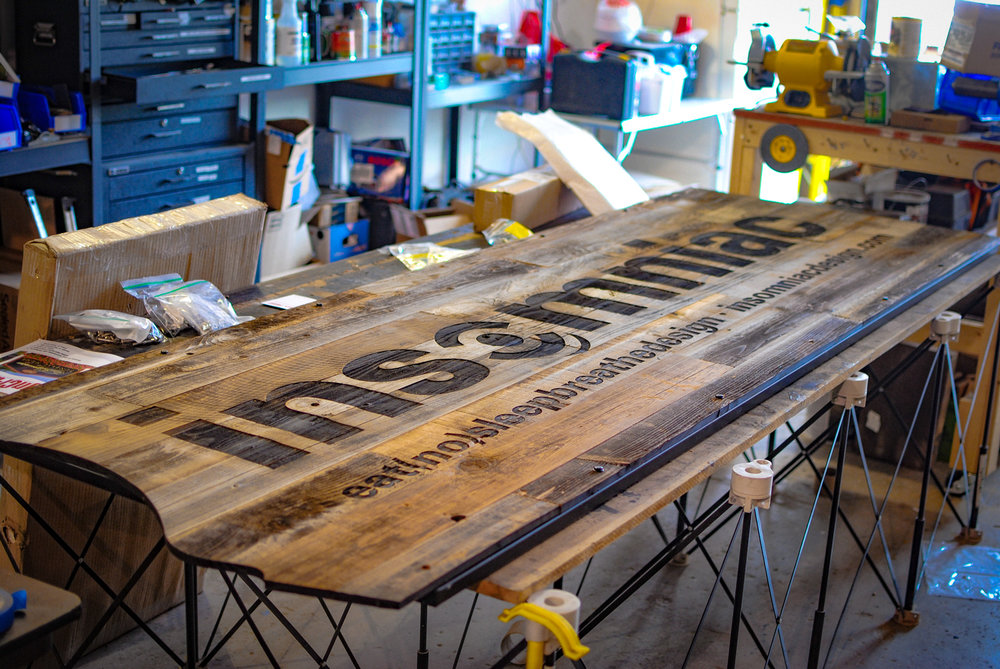 10' long laser engraved sign on reclaimed redwood.