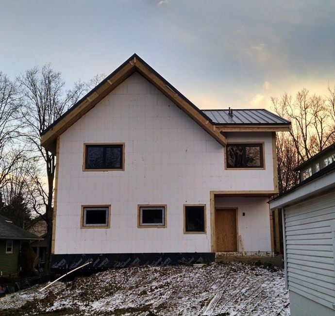 This shows the back of the home with a complete layer of in-so-fast panels applied and passive windows installed.