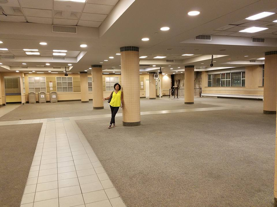 Lourdes standing in the old cafeteria. Image courtesy of Lourdes Rivera-Olsen