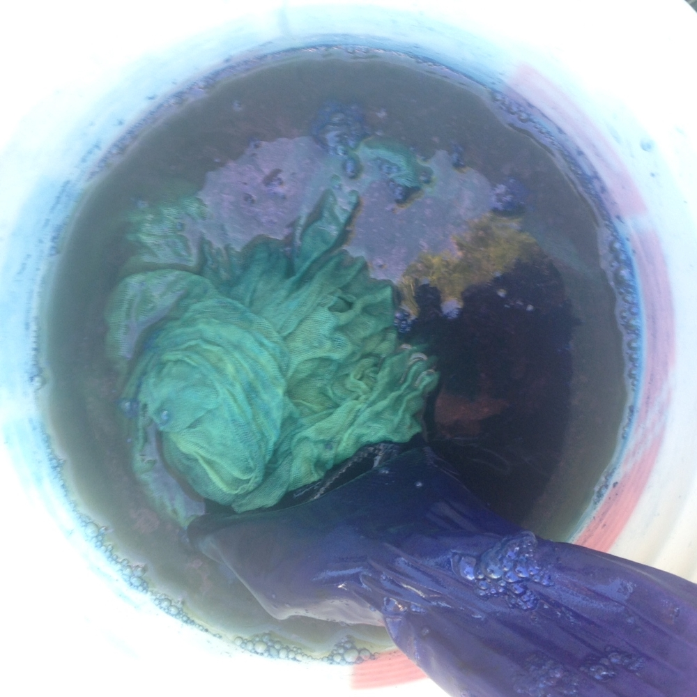 Rinsing out the recently dyed fiber in a bucket of water.  Notice how the fiber is still a bright green after pulling it out of the vat- this is because it hasn't fully oxygenated yet.  If your fiber is blue when you take it from the vat, the pigment will wash right out.