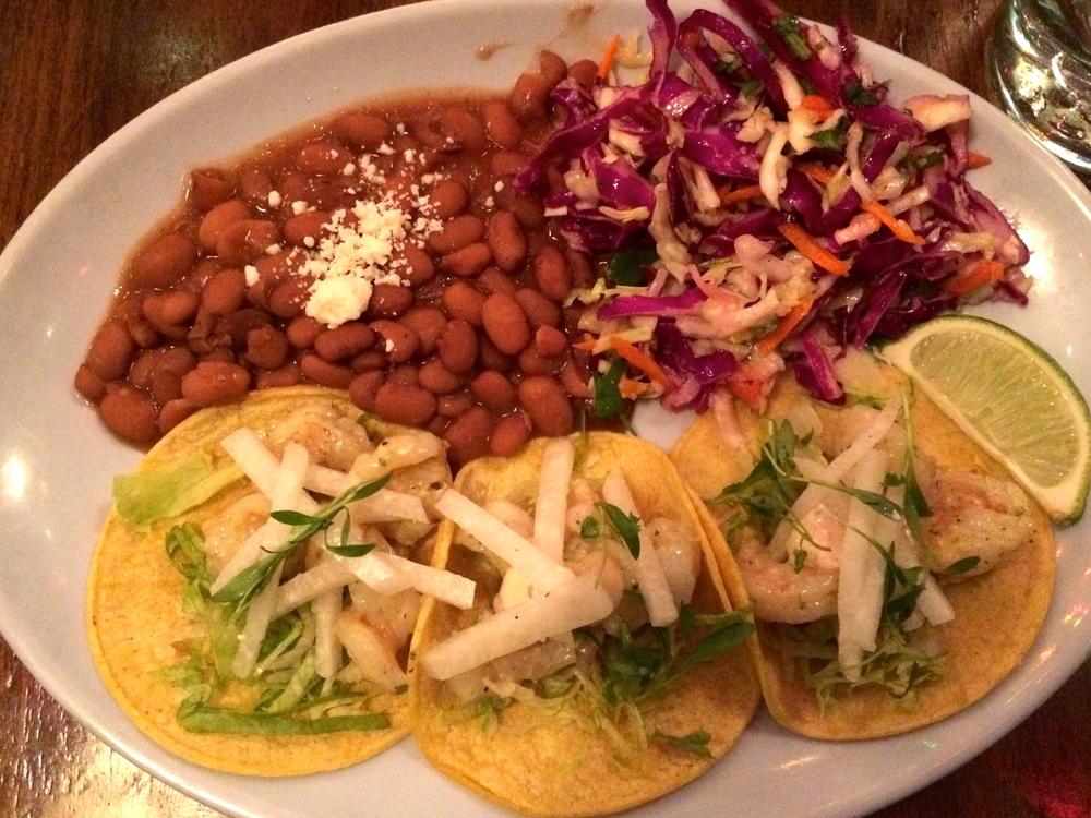 Shrimp tacos, pumpkin seed pesto, cilantro crema, jicama and cilantro served with beans and slaw.