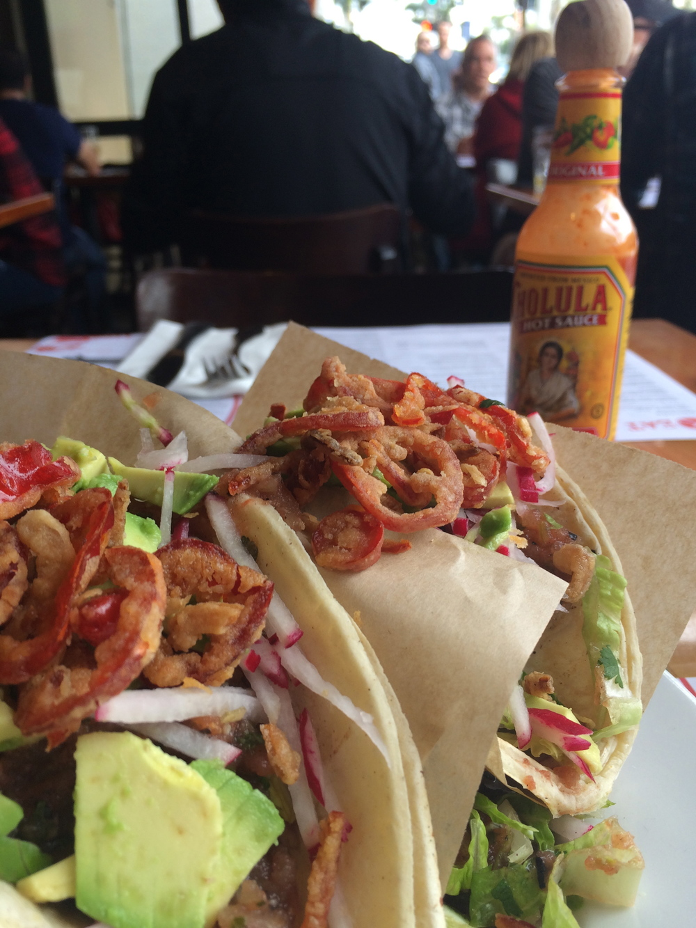 Grilled fish tacos, fresh wild-caught Oregon rock cod, avocado, charred tomato salsa, lime, lettuce, pickled radish, fried fresno chile rings and spice sour cream.