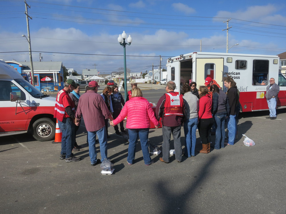 "A spontaneous Thanksgiving prayer during a lull offered by volunteers from various partner groups was interrupted when the Team Leader shouted ""Incoming!"" (meaning a group of residents was walking toward the ERV's.  Workers had to jump back into the vehicles to get the serving lines running again…so much for a break!)."