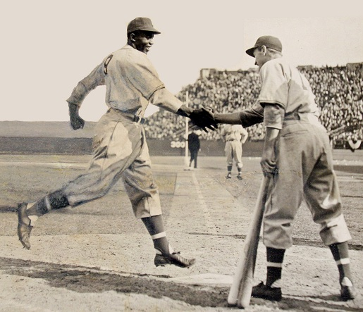 "Jackie Robinson and George ""Shotgun"" Shuba shake hands over home plate, 1946."