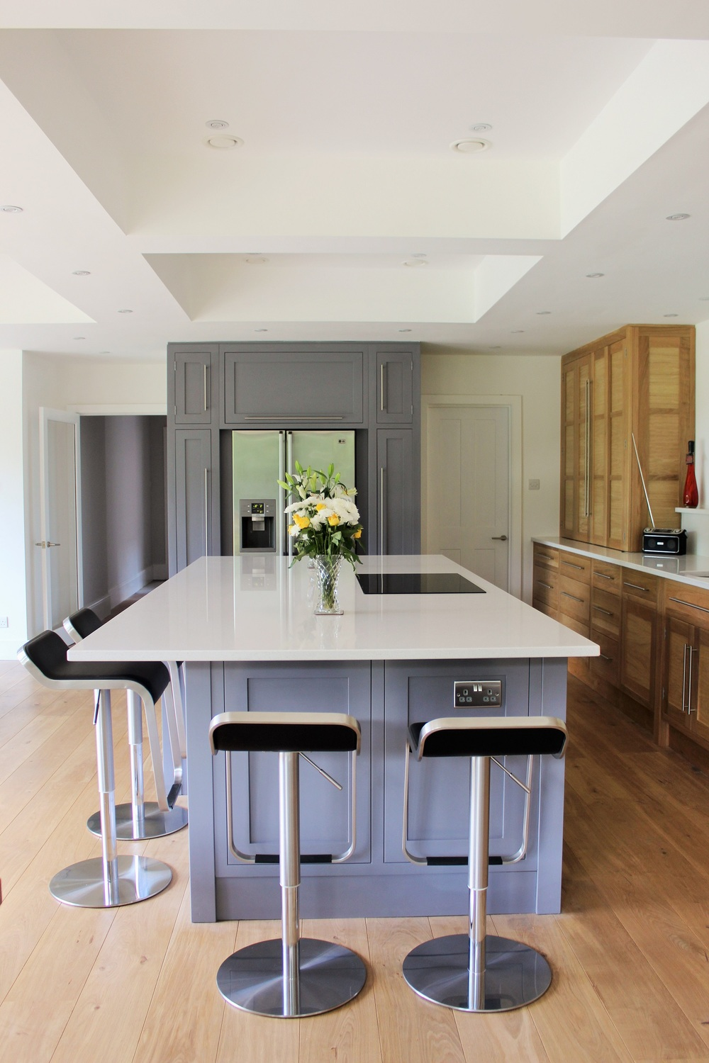 Glanton   A modern Shaker-style kitchen.  Stunning, contemporary and yet traditional, Glanton epitomizes the hand-crafted kitchen. Painted Shaker-style units and dovetailed drawer boxes mixed with natural oak, modern fittings and crisp white stone.   Cabinetry - painted in Collins Bespoke's custom-made Greywillow and Waterborne natural oak finish: £16,000 installed.    Worktops - Quartz - Silestone Blanco Maple polished, with upstands and cut-outs: £5500 installed.    Additions - oak cutlery dividers, integrated recycling units, pull-out larder: £1100 approx. installed.