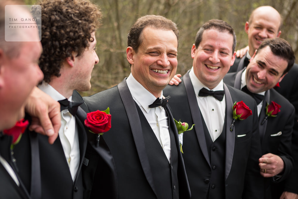 We just love how the rich color in the red rose boutonnieres really pop in this candid groomsmen photo!