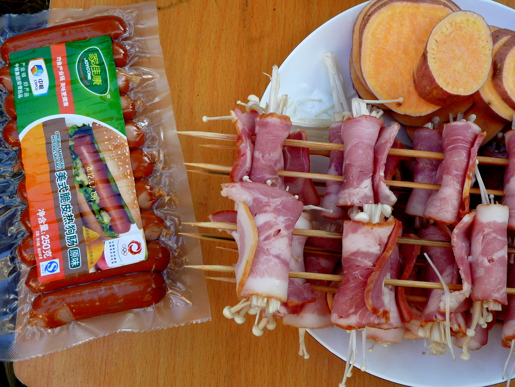 Packaged Chinese sausages and more skewers of meat and sliced yam