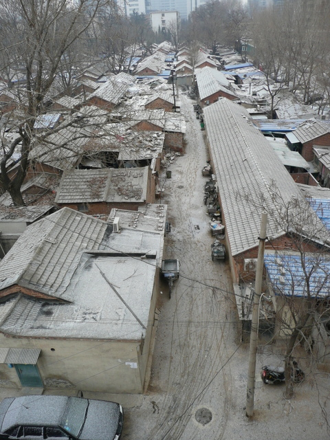 The rooms the traffickers rented in the  siheyuan  extend east, just inside the wall separating the campus from the new apartments on Chengfu Road. The men struggle to drag Rick's body into and through a train of adjoining rooms to the last one.  This choice of a hideout, near the LiNai Apartments, was perfect for surveilling Rick and Mai. Now that they have the captive, they remove plywood covering another door in the last room, leading to a vacant storage shed on the corner of the hutong directly beneath Mai's apartment and adjacent to the car gate. They throw him on a mattress in the cold room and shut him in alone.  He lies there, not moving, breathing irregularly. A black bag covers his head. His powerful arms are tied behind with zip ties, as are his ankles. His mouth is taped shut.