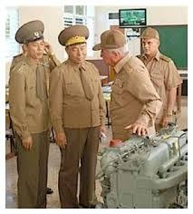 Col. PANG Myong Cha, Deputy Airport Director, left, RI Yongho, Director General Bureau of Surveillance, Chief to General Staff of Korean People's Army DPRK, right, discuss aeroplane maintenance with Russian mechanics.