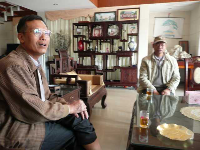 I draw on my travels in China to provide me with abundant detail for the characters and settings. In the scene at the villa, I used a visit to the opulent sitting room of Director Xie Keying, Chinese Penjing craftsman, Chinese Penjing Artists Association Vice President and Guangdong Province Penjing Association Routine Vice Chairman and Secretary General at his private residence.   The elaborate etagere at the back of the room was reproduced in the illustration for the story.  Pictured here is my contact on the left Master Chen and Master Jia Ji on the right.  I interviewed Master Chen as well and  that story was published in the global bonsai magazine Bonsai Focus.