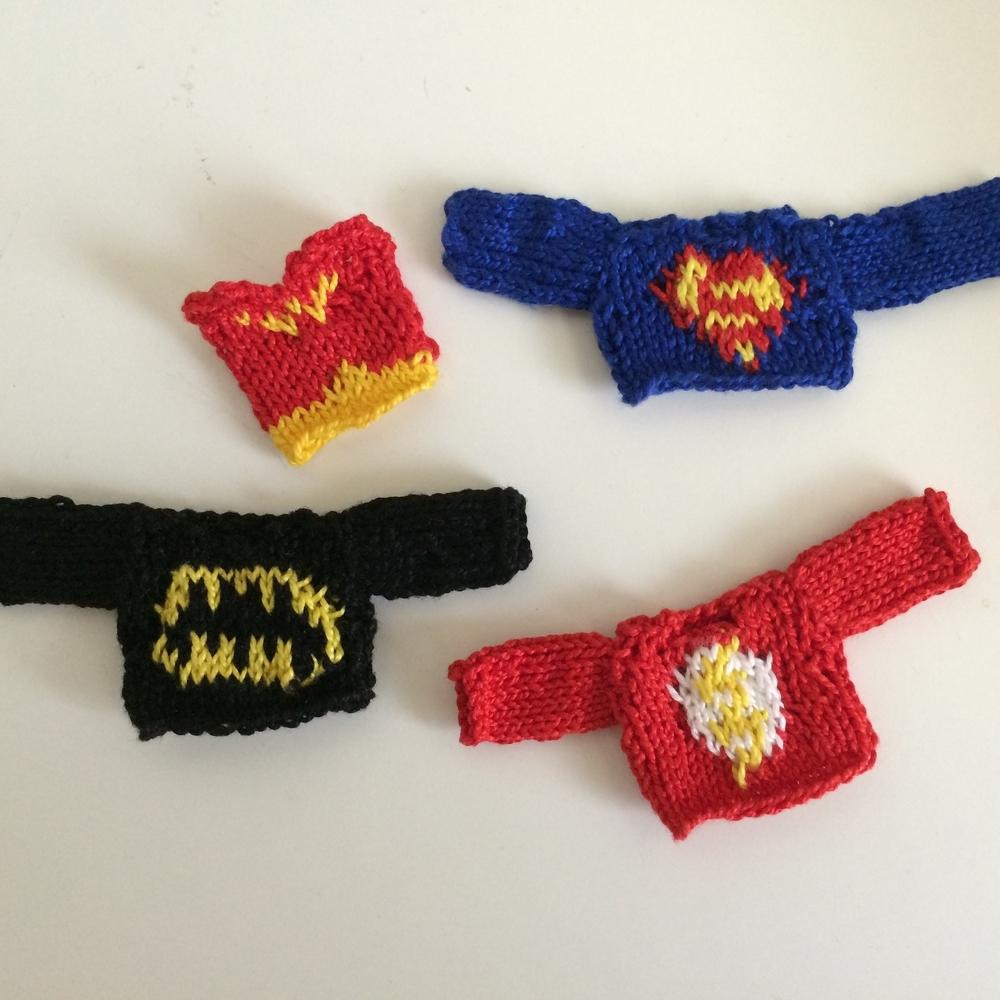 Miniature sweaters with superhero logos