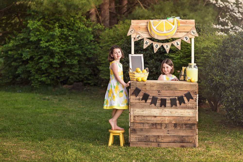 sisters-laughing-together-lemonade-stand-maryville-photographer.jpg