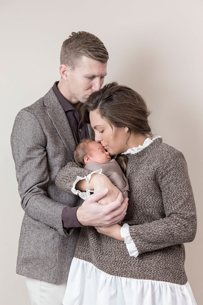 newborn-with-parents-sweet-kiss-pose.jpg