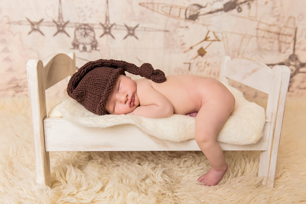 Newborn sleeping on bed