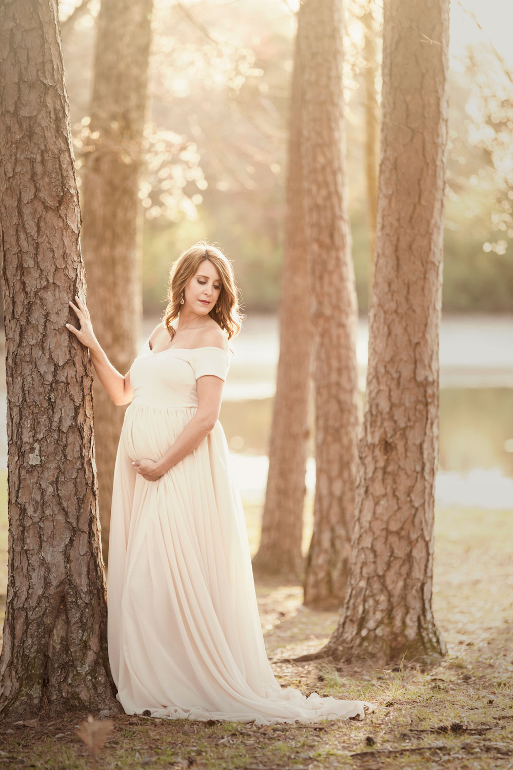 Knoxville mom posing in grove of trees for maternity picture